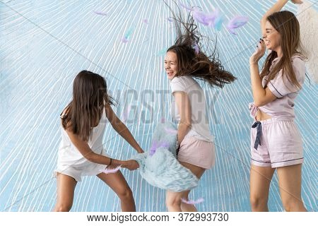 Pillow Fight. Beautiful Smiling Female Models In Stylish Pajamas Playing And Fighting With Pillows A