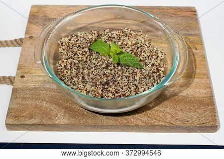 Closeup On Glass Bowl With Cooked Tri-color Quinoa Quinoa On Wooden Cutting Board, Decorated With Mi