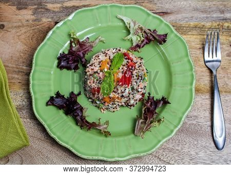 Closeup On Green Plate With Tri-color Quinoa Salad On Wooden Table, And A Fork - Quinoa Is A Pseudog