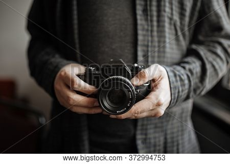 Male In Shirt Man Hands Holds Retro Camera. Horizontal. Close Up