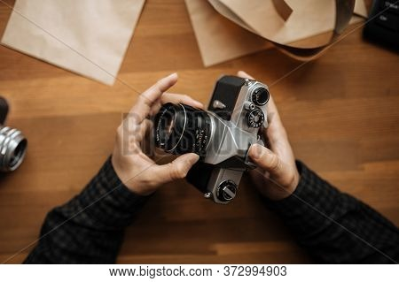Male Man Hands Adjusts The Lens Pentax Retro Camera On A White Table. Horizontal