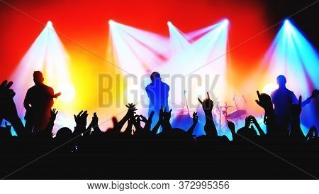 Blurred Silhouettes Of Rock Band Musicians On Stage And Crowd At A Concert