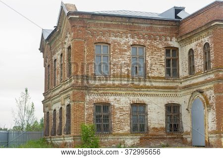 The Abandoned House Has 2 Floors. Large Windows With Bars On A Brick Old House. The Estate Of The La