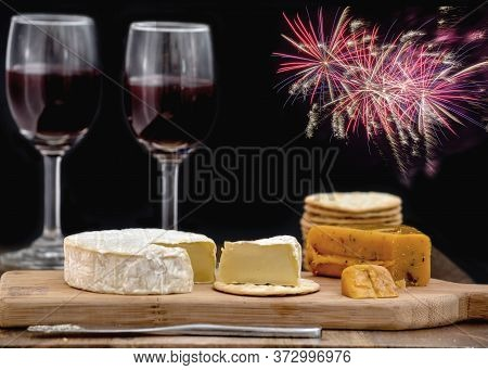 Brie And Hot Pepper Jack Cheese On Wooden Cheese Board, Accompanied By Crackers And Two Glasses Of R