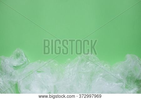 Layout On A Green Background From Plastic Disposable Cups And Plastic Bags. Caring For The Environme