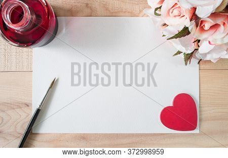 Work Space Watercolor Paper Or Note Paper With Red Ink,red Heart, Brush And Bouquet Of Roses On Wood