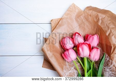 Brightly Pink Tulips Lie On Kraft Paper On A Light Blue Wooden Background.