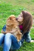 Dog breed Pomeranian licking a young woman in face poster