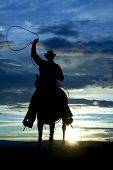 A cowboy is riding forward in the sunset with a rope above his head. poster