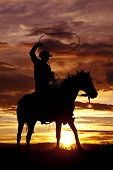 A cowboy is sitting on his horse in the sunset and swinging a rope. poster
