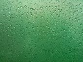 Water drops flowing on a green umbrella. Close-up shot poster