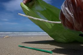 Picking up plastic trash from beach. Plastic bottles, bags, straws and cups litter a pristine beach. Environmental clean up