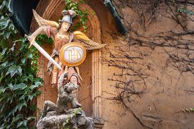 Statue Of Angel With Sword And Shied Fighting Devil In The Fuggerei Walled Enclave Within The City O