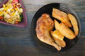Chicken Thigh With French Fries On Blue Gray Wooden Background. Chicken Thigh On Black Plate. Rustic
