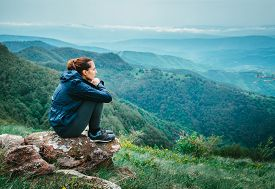 Sad Depressed Woman Sitting On Rock In Raincoat. Rear View Of Depressed Woman. Woman In Depression.