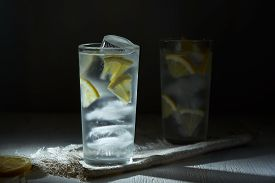 Two Glasses Of Ice Cold Lemonade With Lemon Slices And Ice On Linen Napkin On Black Background In Bl