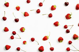 Berries Of Ripe Strawberries And Cherries Are Scattered On A White Table With Copy Space. Top View.