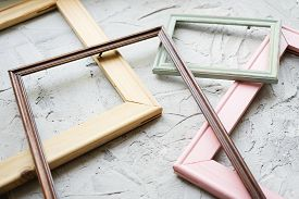 Several Empty Wooden Frames On A Concrete Background.