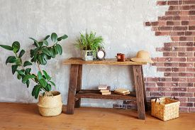 Wicker Hat, Retro Camera And Travel Guides On A Wooden Console In A Loft-style Interior. Travel Dela