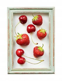 Ripe Strawberries And Cherries In A Vintage Frame Isolated On White Background.