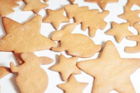 Freshly Baked Rabbit-shaped Gingerbread On Parchment. Traditional Christmas Pastries. The Process Of
