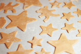 Star-shaped Gingerbread Cookie With On Parchment. Christmas Dessert. The Process Of Baking Cookies.