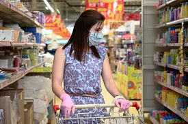 Woman Wears Protective Mask And Gloves While Shopping At Supermarket. Horizontal Orientation.