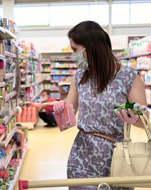 Woman Wears Protective Mask And Gloves While Shopping At Supermarket. Vertical Orientation
