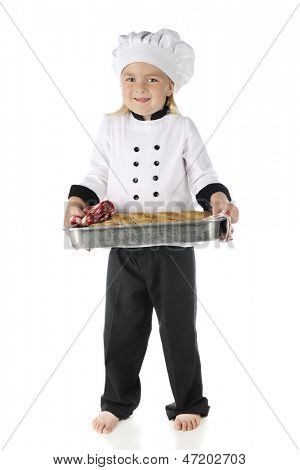 "An adorable preschool ""chef"" happily holding a load of bread in its baking pan.  On a white background."