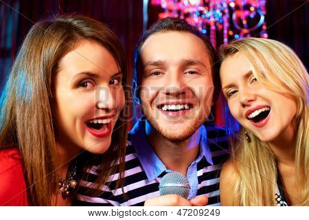 Portrait of happy freinds singing in microphone in the karaoke bar