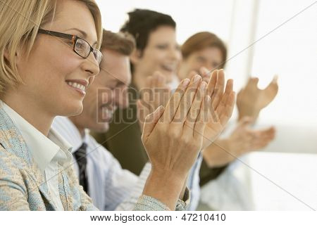 Happy businesswoman with colleagues applauding at conference table