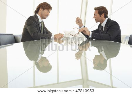 Side view of angry businessmen with crumpled paper balls at conference table