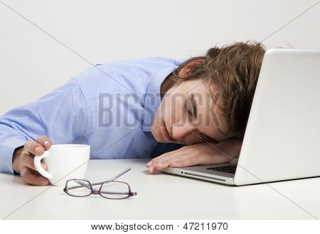 Exhausted businessman in the office sleeping over the laptop