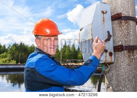 Caucasian Senior Worker Man Turning The Power Switch