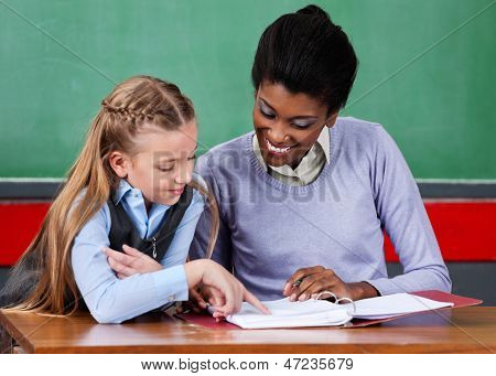 Young African American female teacher assisting schoolgirl at desk in classroom