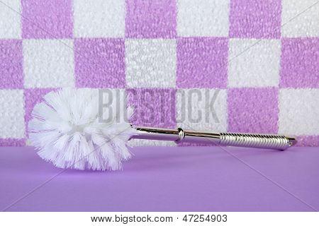 Toilet brush on tile wall background