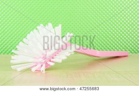 Toilet brush on green background