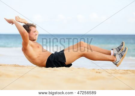 Fitness man doing crunches sit-ups on beach exercise outside. Fit male athlete exercising sit ups training on beautiful beach. Handsome sport model in cross training workout outdoors. poster