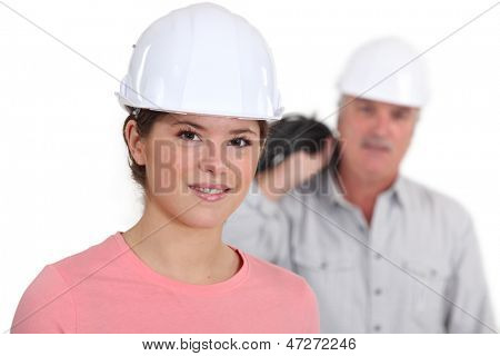 Portrait of a young tradeswoman with her boss in the background