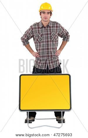 Worker stood by blank road sign