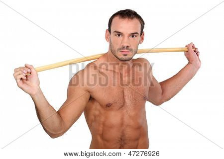 bare-chested man showing off with stick against white background