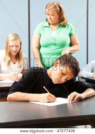 Young mixed race student taking a test in school, teacher and other student in background.