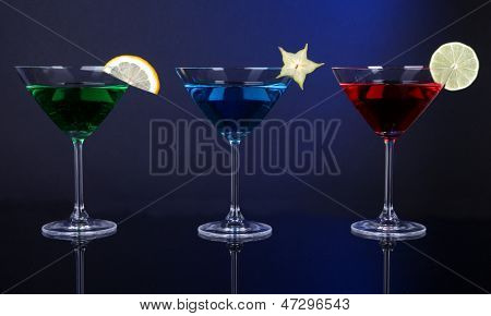 Alcoholic cocktails in martini glasses on dark blue background poster