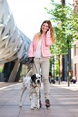 Portrait of a cute female walking her dog outdoors and talking on mobile phone poster