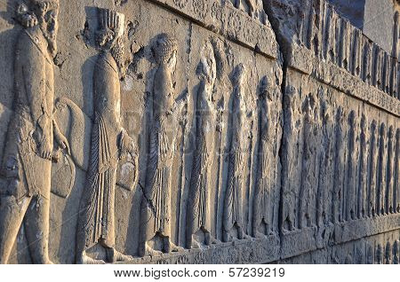 Line of carved Persians on the stone wall in Persepolis