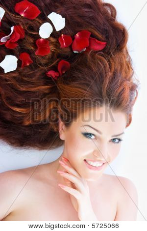 Close-up beautiful luxury fresh bright young lady lying in studio shot with rose petals in her red (brown) long hair poster