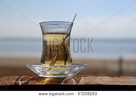 A glass of turkish tea by the sea