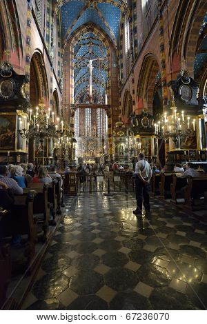 KRAKOW, POLAND - SEPTEMBER 15, 2013: People in the Church of Our Lady Assumed into Heaven, also known as St. Mary's Basilica. XV century wooden altarpiece by Veit Stoss is the highlight of interior