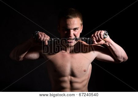 Portrait Of A Young Muscular Guy With A Metal Chain In His Mouth.