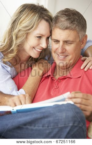 Mid age couple reading book together